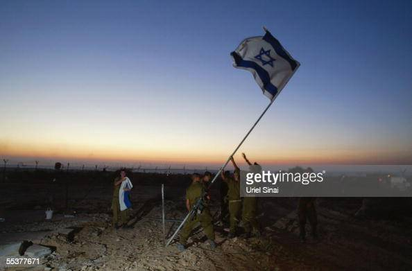 Israeli soldiers take part in a flaglowering ceremony as they prepare to withdraw from the army headquarters September 11 2005 in Gush Katif in the...