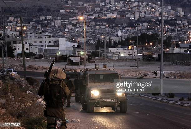 Israeli soldiers take part in a search operation for three Israeli teenagers believed kidnapped by Palestinian militants early on June 18 2014 in the...
