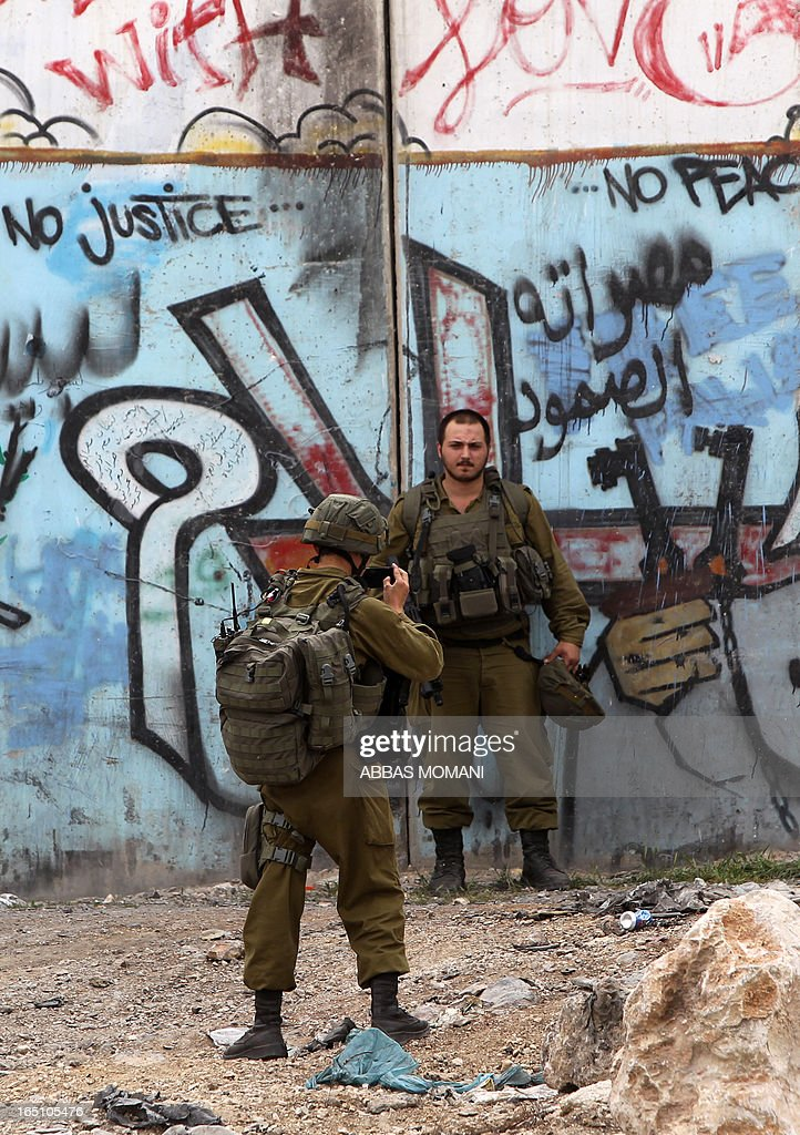 Israeli soldiers take pictures in front of the Israeli separation barrier covered with grafittis during clashes with Palestinians following a rally commemorating the 37th anniversary of 'Land Day', on March 30, 2013 near the Qalandia checkpoint in the Israeli occupied West Bank. Nearly 200 Palestinians clashed with Israeli forces in Qalandia, who responded with tear gas.