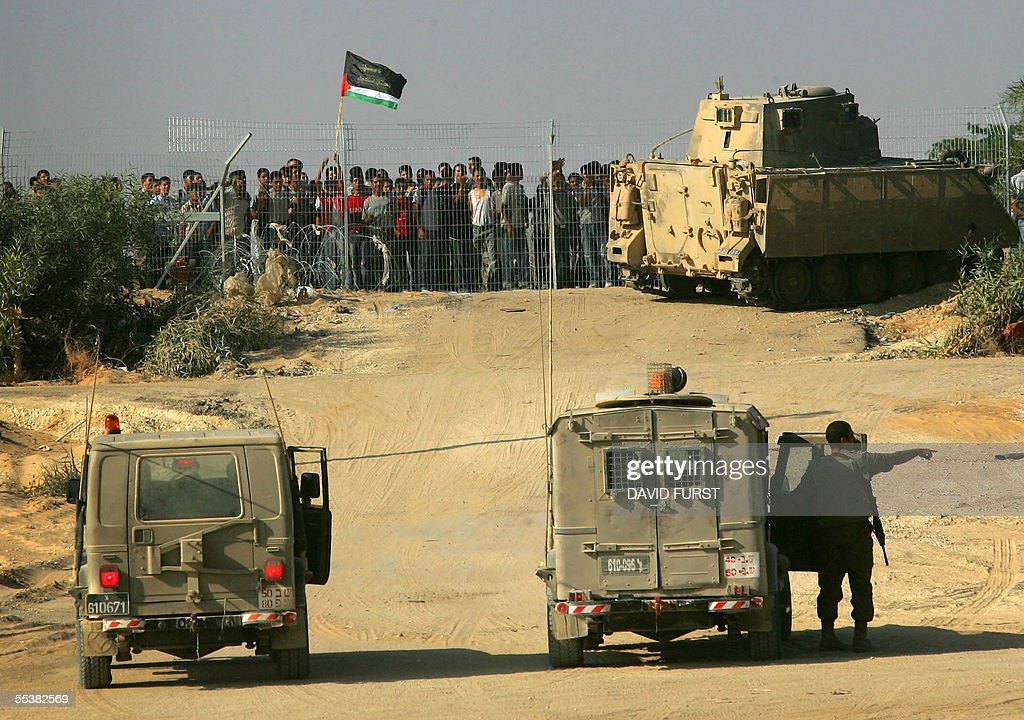Israeli soldiers take position 12 September 2005 around Netiv Haasara after Palestinian youths approached the fence surrounding the former northern...