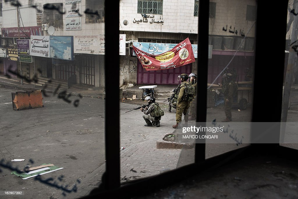 Israeli soldiers take position during clashes with Palestinian protesters in the old city of Hebron on March 1, 2013 following a protest demanding the reopening of Shuhada Street, the one-time heart of the city. Flanked by a handful of Jewish settlement enclaves, the Shuhada Street was partially closed off in 1994 after local settler Baruch Goldstein opened fire on Muslim worshippers at the city's Al-Ibrahimi mosque, killing 29 of them.
