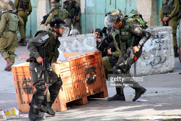 Israeli soldiers take position during clashes with Palestinians who protest the eviction of settlers from the building last year as Jewish settlers...
