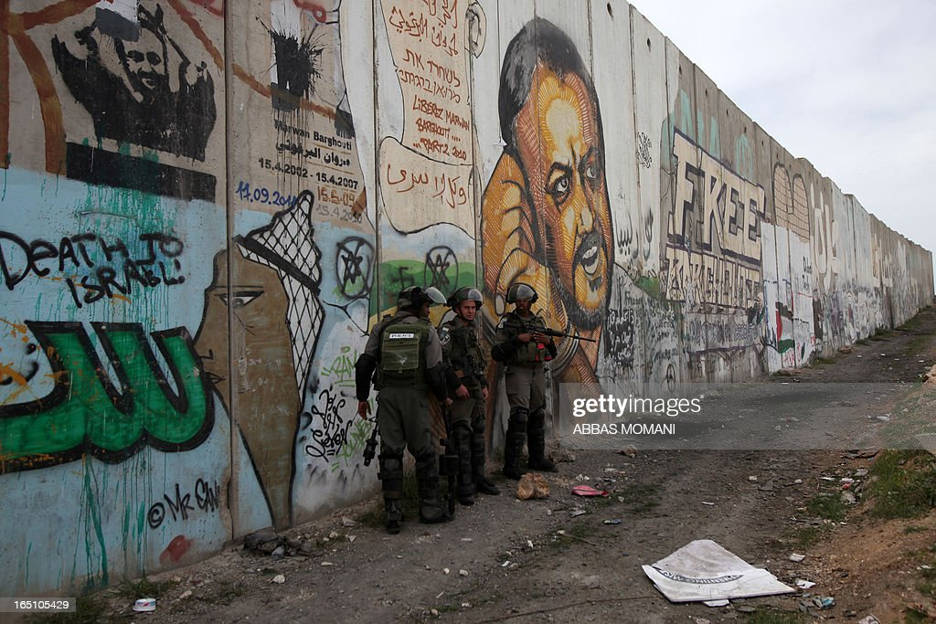 Israeli soldiers take position in front of the Israeli separation barrier covered with grafittis during clashes with Palestinians following a rally commemorating the 37th anniversary of 'Land Day', on March 30, 2013 near the Qalandia checkpoint in the Israeli occupied West Bank. Nearly 200 Palestinians clashed with Israeli forces in Qalandia, who responded with tear gas.