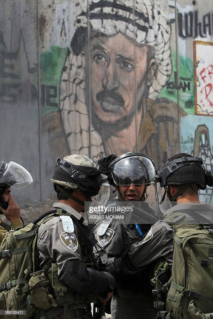 Israeli soldiers talk in front of the Israeli separation barrier during clashes with Palestinians following a rally commemorating the 37th anniversary of 'Land Day', on March 30, 2013 near the Qalandia checkpoint in the Israeli occupied West Bank. Nearly 200 Palestinians clashed with Israeli forces in Qalandia, who responded with tear gas.