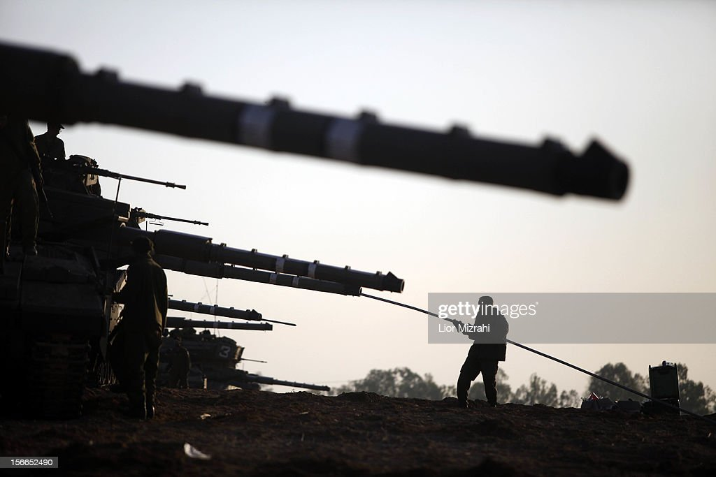Israeli soldiers tend to their tanks in a deployment area on Israel's border with the Gaza Strip on November 18 in Israel Israeli shelling of Gaza...