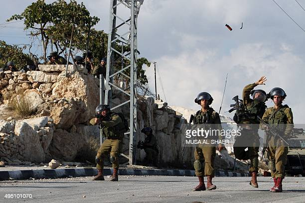 Israeli soldiers throw a flash grenade during clashes with Palestinian demonstrators following the funeral of eightmonthold Palestinian boy Ramadan...
