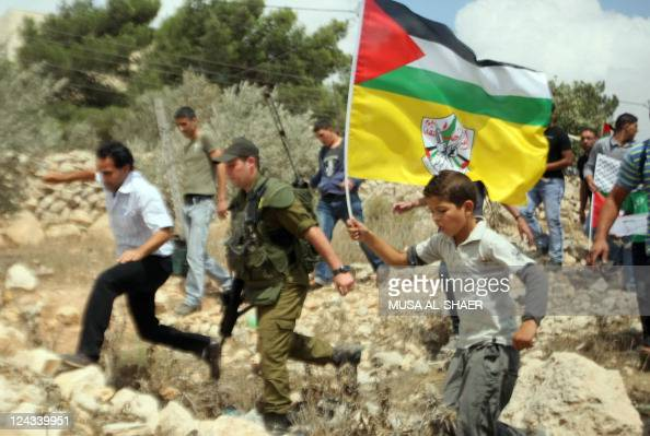 Israeli soldiers try to disperse Palestinian demonstrators waving national and Fatah flags during a protest against Israel's controversial separation...