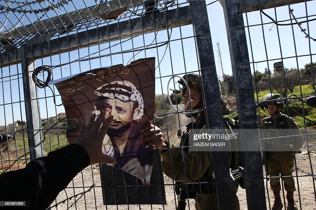 Israeli soldiers try to remove a picture of the late Palestinian leader Yaser Arafat, fixed to the entrance of the Israeli settlement of Karmi Tsour, near Beit Omar village north of the West Bank town of Hebron on January 31, 2015. The Israeli government on Friday published tenders to build 430 new settler homes in the occupied West Bank, the head of an NGO that monitors settlement activity told AFP. Israel occupied the West Bank in the 1967 Six-Day war. Building settlements there is illegal under international law and opposed by the United States and the international community as an obstacle to an eventual peace deal with the Palestinians. AFP PHOTO/ HAZEM BADER