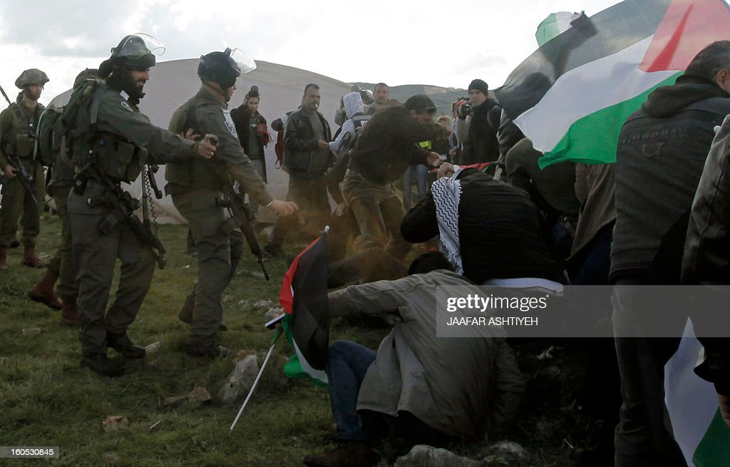 Israeli soldiers use pepper spray towards Palestinians demonstrators as they forcefully remove them from a new camp set up to protest against Jewish settlements near the West Bank village of Burin on February 2, 2013. An AFP correspondent said the Israeli army used tear gas and violence to remove hundreds of people who had set up four temporary huts and three tents near Burin, south of Nablus in the occupied West Bank, in a third attempt at the novel form of protest against Jewish settlements. AFP PHOTO /JAAFAR ASHTIYEH