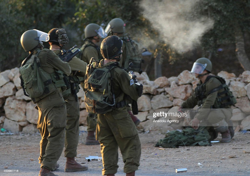 Israeli soldiers use teargas to disperse Palestinians during the protest against the Israeli attacks on Gaza, Silvad village in Ramallah, West Bank on August 22, 2014.