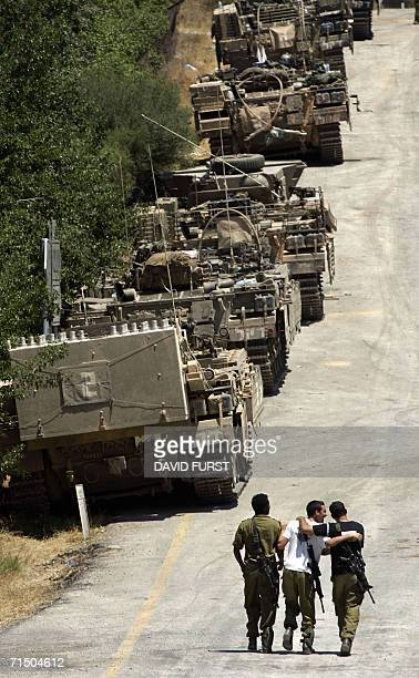Israeli soldiers walk arminarm past a column of armored personnel carriers at a staging area located along the Israeli Lebanese border 23 July 2006...