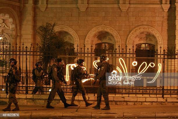 Israeli soldiers walk before a lighted sign reading 'Ramadan Kareem' during clashes with stonethrowing Palestinian protesters at a section of the...