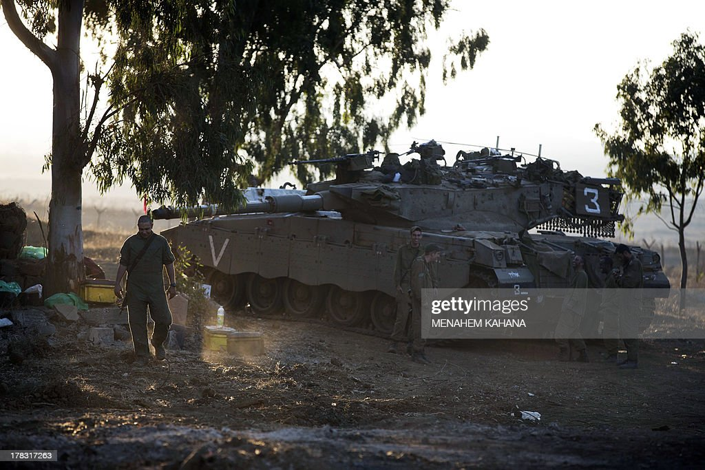 Israeli soldiers walk next to a Merkava tank stationed in a deployment training area in the Israeli-annexed Golan Heights near the border with Syria on August 29, 2013. The Israeli cabinet authorised on August 28 a partial call-up of army reservists amid growing expectations of a foreign military strike on neighbouring Syria, army radio reported. The unspecified number of troops are attached to units stationed in the north of the country, which borders both Lebanon and the Golan Heights.