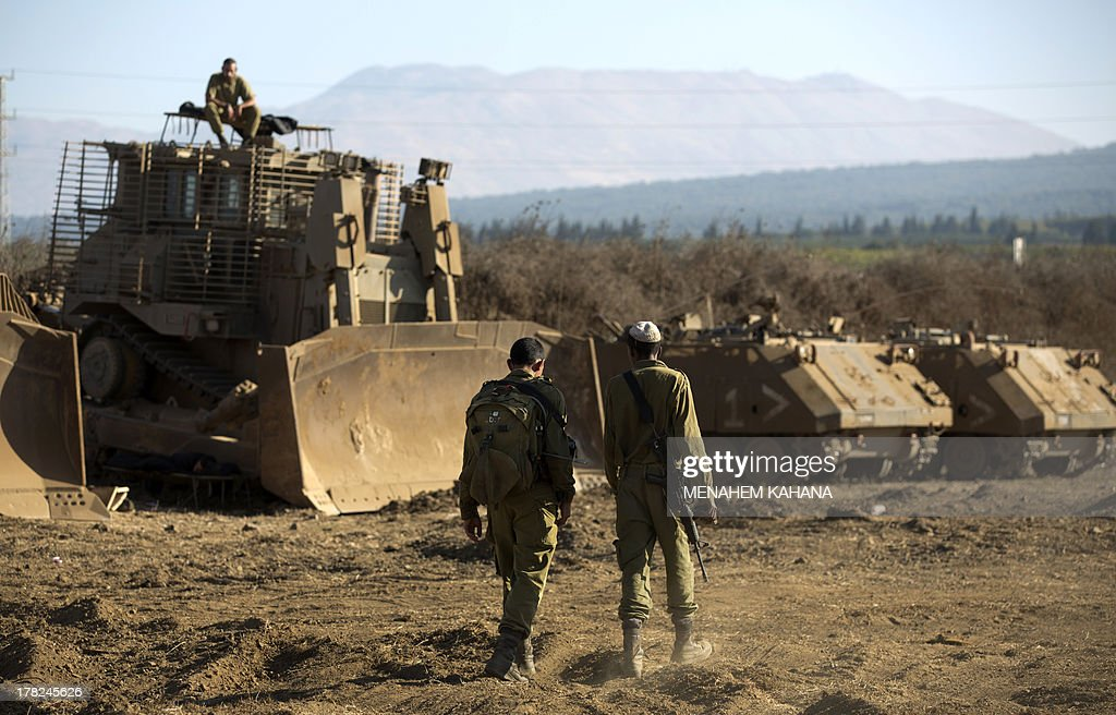 Israeli soldiers walk next to an armoured bulldozer in an army deployment training area in the Israeli-annexed Golan Heights near the border with Syria on August 28, 2013. Israel will strike back 'fiercely' if Syria attacks the Jewish state, Prime Minister Benjamin Netanyahu said, as the US mulled military action against President Bashar al-Assad's regime.