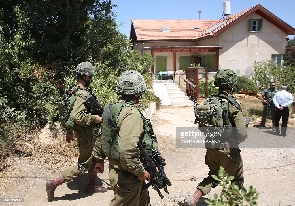 Israeli soldiers walk outside a house in the Jewish settlement of Kiryat Arba in the occupied West Bank where a 13-year-old Israeli girl was fatally stabbed in her bedroom on June 30, 2016. A Palestinian attacker stabbed a 13-year-old girl to death at her home in the Jewish settlement outside the city of Hebron before being shot dead by security guards, the Israeli army said. KAHANA