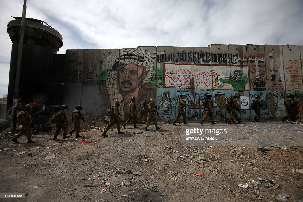 Israeli soldiers walk past the Israeli separation barrier covered with grafittis as they take position during clashes with Palestinians following a rally commemorating the 37th anniversary of 'Land Day', on March 30, 2013 near the Qalandia checkpoint in the Israeli occupied West Bank. Nearly 200 Palestinians clashed with Israeli forces in Qalandia, who responded with tear gas.