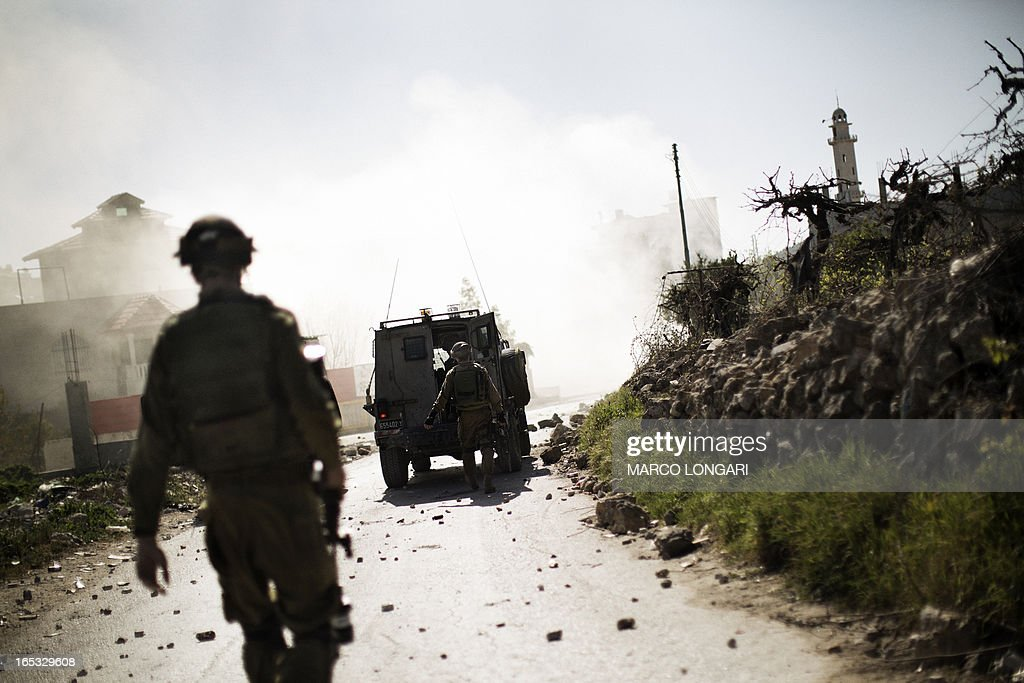 Israeli soldiers walk toward a cloud of tear gas during clashes with Palestinian stone throwers at the al-Arub refugee camp North of the West Bank city of Hebron on April 3, 2013. Defence Minister Moshe Yaalon warned that Israel would respond to any attacks on its territory and not allow its people to come under fire 'in any form'. AFP PHOTO/MARCO LONGARI