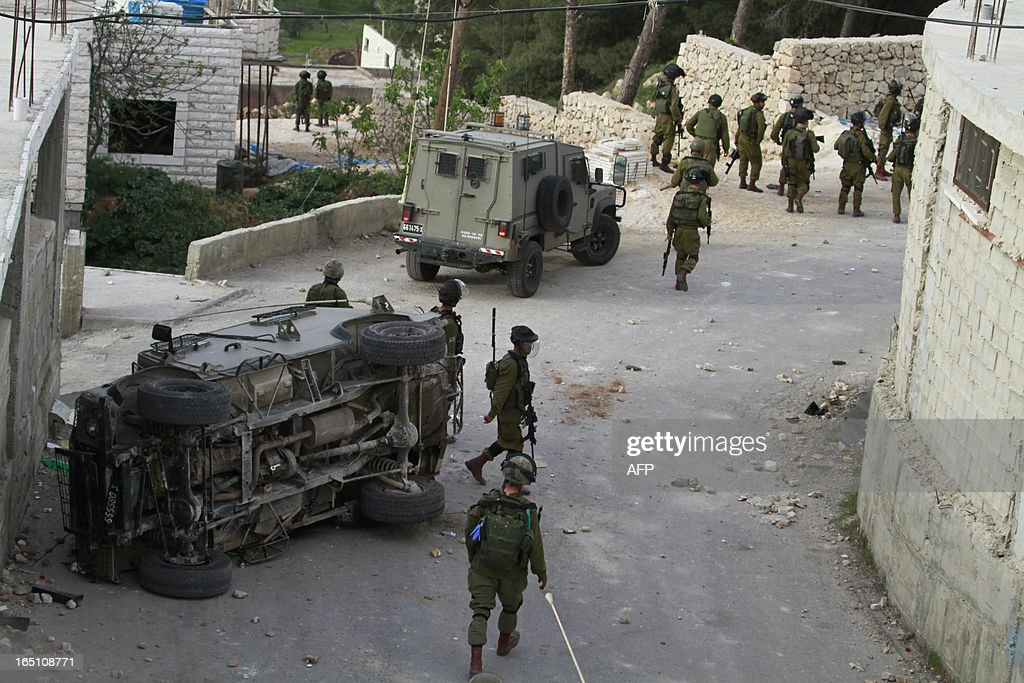 Israeli soldiers walk towards Palestinian protesters after an army vehicle returned during clashes following a rally marking Land Day in the al-khader village near the West Bank town of Bethlehem on March 30, 2013. The annual demonstrations mark the deaths of six Arab Israeli protesters at the hands of Israeli police and troops during mass protests in 1976 against plans to confiscate Arab land in the northern Galilee region.