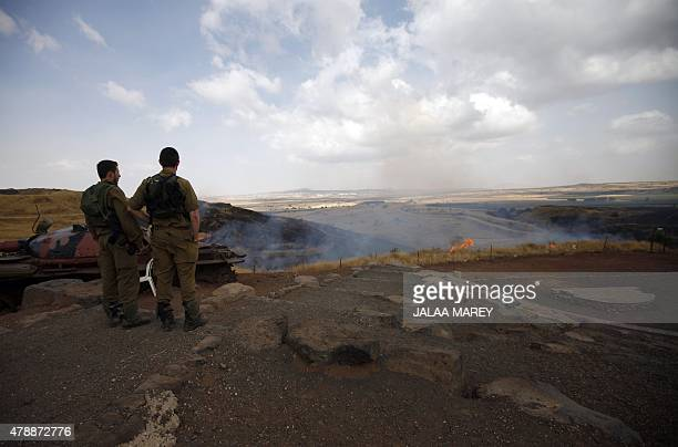 Israeli soldiers watch the flames on a mountain side in the ElRom settlement in the Israeliannexed Golan Heights on June 28 after it was hit by a...