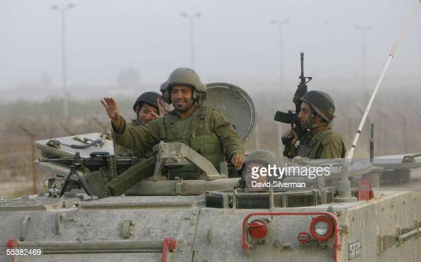 Israeli soldiers wave as their armored personnel carrier withdraws on September 12 2005 through the Kerem Shalom crossing into Israel from the...