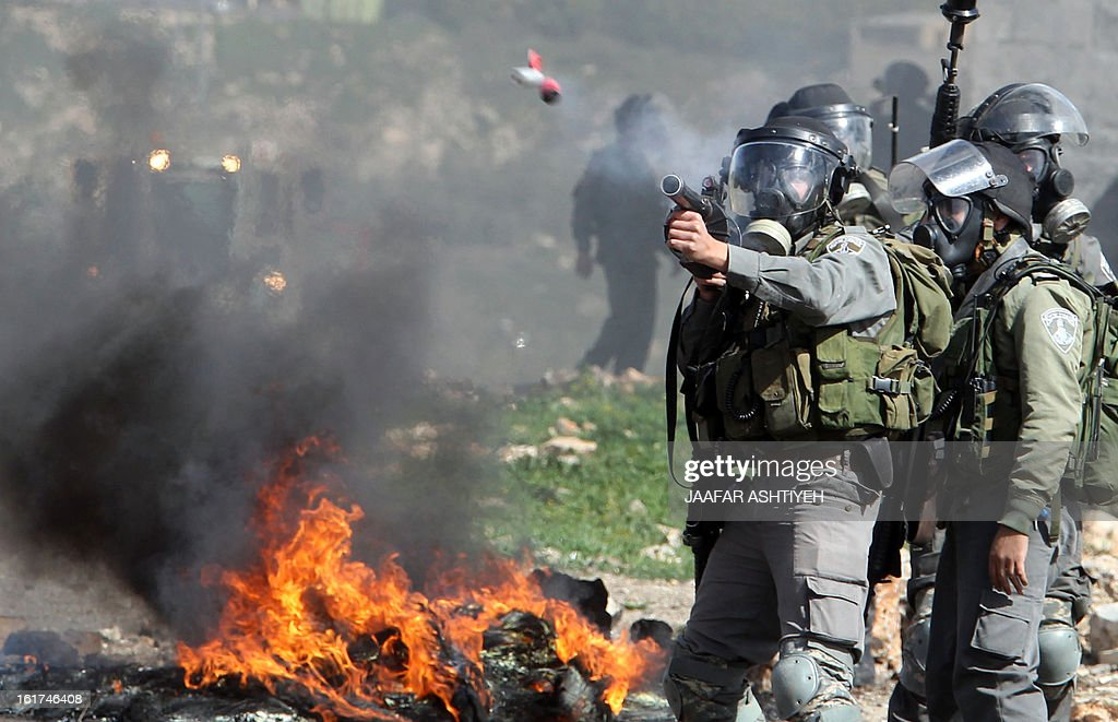 Israeli soldiers wearing gas masks fire tear gas towards Palestinian protesters during clashes following a demonstration against the expropriation of Palestinian land by Israel on February 15, 2013, in the village of Kafr Qaddum, near the occupied West Bank city of Nablus.