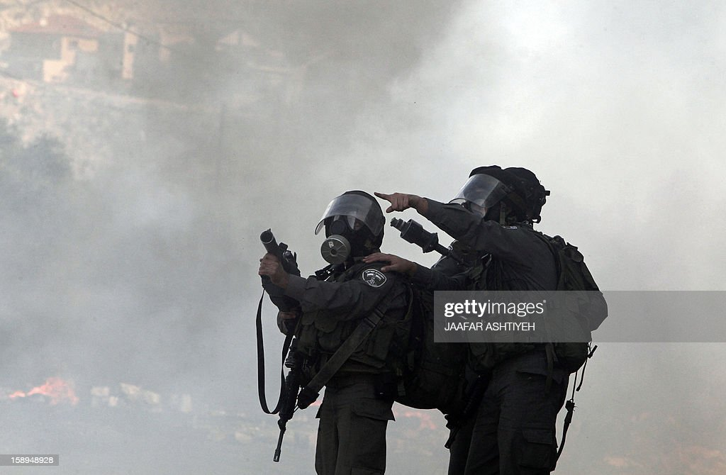 Israeli soldiers wearing gas masks point towards Palestinian protestors as they stand near smoke rising from burning rubber tyres during clashes with Palestinian protesters at a demonstration against the expropriation of Palestinian land by Israel in the village of Kfar Qaddum, near the occupied West Bank city of Nablus, on January 4, 2013.