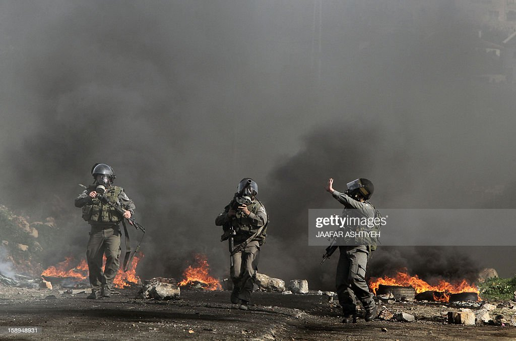 Israeli soldiers wearing gas masks walk through black smoke rising from burning rubber tyres during clashes with Palestinian protesters as they demonstrate against the expropriation of Palestinian land by Israel in the village of Kfar Qaddum, near the occupied West Bank city of Nablus, on January 4, 2013. AFP PHOTO/JAAFAR ASHTIYEH
