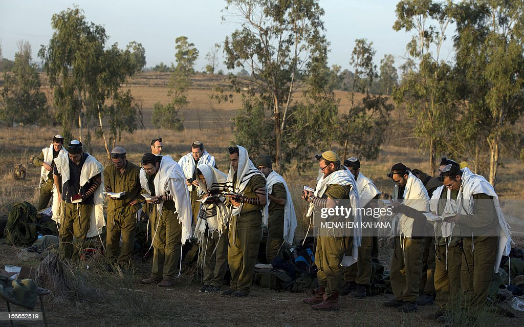 Israeli soldiers wearing 'Talit' (prayer shawls) and 'Tefilin' (phylacteries) conduct morning prayers at an Israeli army deployment area near the Israel-Gaza Strip border in preparation for a ground operation in the Palestinian coastal enclave on November 18, 2012. Prime Minister Benjamin Netanyahu said that Israel is ready to 'significantly expand' its operation against militants in the Hamas-run Gaza Strip as it entered its fifth day.