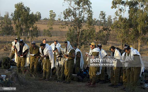 Israeli soldiers wearing 'Talit' and 'Tefilin' conduct morning prayers at an Israeli army deployment area near the IsraelGaza Strip border in...