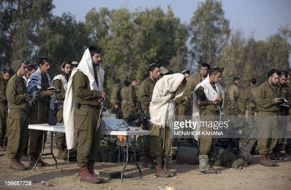 Israeli soldiers wearing 'Talit' and 'Tefilin' conduct morning prayers at an Israeli army deployment area near the IsraelGaza Strip border as they...