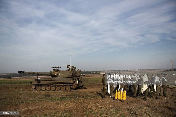 Israeli soldiers wearing 'Tallit' and 'Tefilin' perform morning prayers next to their tank at an artillery battery deployment near the IsraelGaza...