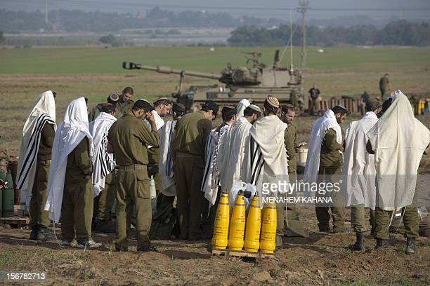 Israeli soldiers wearing 'Tallit' and 'Tefilin' perform morning prayers next to a tank at an artillery battery deployment near the IsraelGaza Strip...