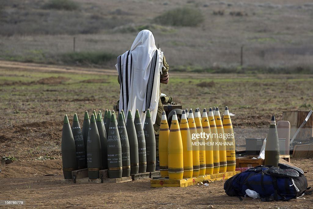 Israeli soldiers wearing 'Tallit' (prayer shawls) and 'Tefilin' (phylacteries) perform morning prayers at an artillery battery deployment near the Israel-Gaza Strip border on November 21, 2012. Fighting raged on both sides of Gaza's borders Wednesday despite intensified efforts across the region to thrash out a truce to end a week of violence that has cost 136 Palestinian and five Israeli lives. AFP PHOTO / MENAHEM KAHANA