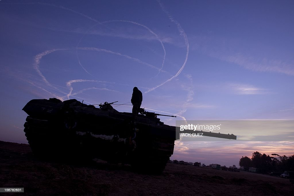 Israeli tanks are stationed at an Israeli army deployment area near the Israel-Gaza Strip border with smoke trail in the background on November 21, 2012. Fighting raged on both sides of Gaza's borders Wednesday despite intensified efforts across the region to thrash out a truce to end a week of violence that has cost 136 Palestinian and five Israeli lives.