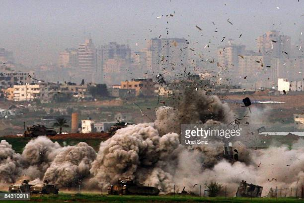 Israeli tanks destroy a house on January 16 2009 in Gaza seen from the Israeli side of the border Yesterday saw an Israeli attack using white...