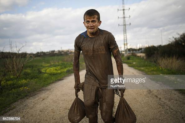 Israeli teenagers carry heavy sandbags after crawling through mud during an annual combat fitness training competition in preparation for the...