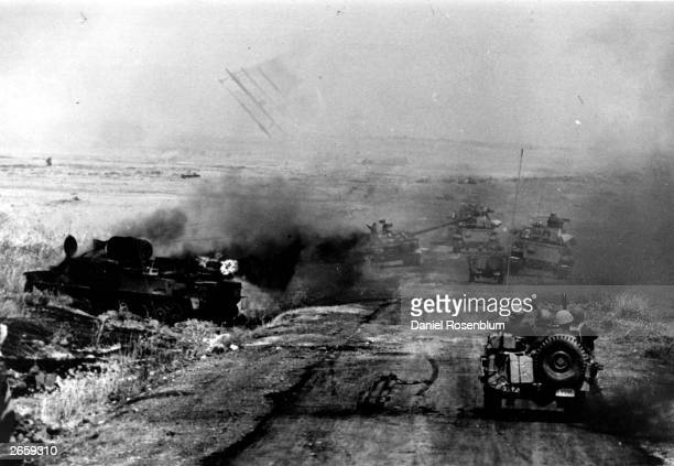 Israeli troops advance during the battle for the Golan Heights during the Yom Kippur War A Syrian tank blazes by the roadside