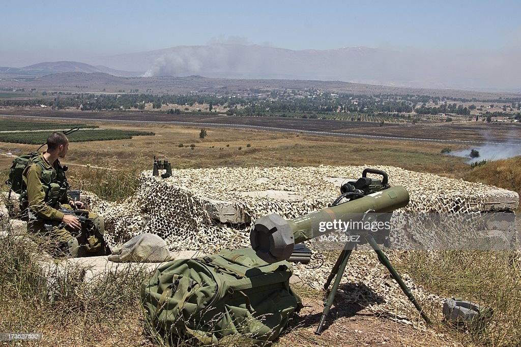 Israeli troops keep position along the ceasefire line with Syria as smoke billows after mortar fire from inside war-torn Syria hit the Israeli-occupied Golan Heights on July 16, 2013 causing several wildfires to break out. The apparently stray rounds struck as Syrian rebels and regime forces battled near Quneitra which lies in no-man's land, the correspondent reported. Israel, which remains technically at war with Syria, seized 1,200 square kilometres (460 square miles) of the strategic plateau during the 1967 Six-Day War, which it later annexed in a move never recognised by the international community.