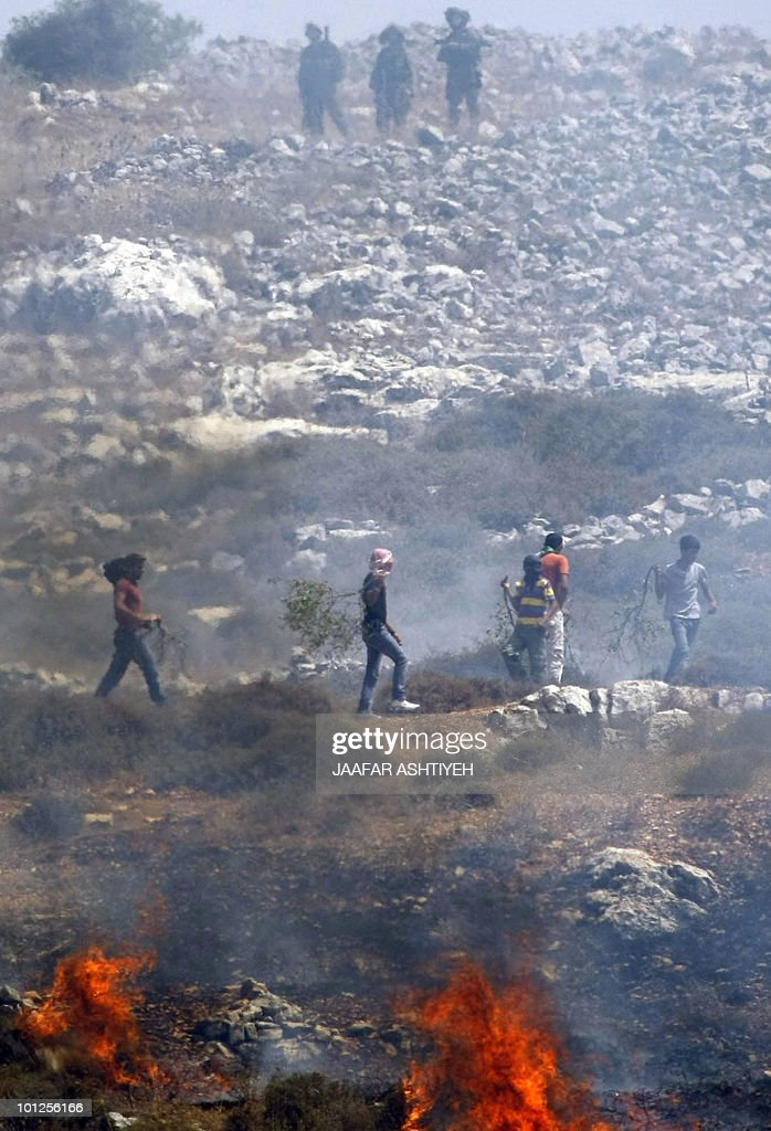 Israeli troops (top) stand guard as Palestinian youths demonstrate against the expansion of Jewish settlements in the occupied West Bank and Israeli troops in the village of Iraqi Burin, near Nablus, on May 29, 2010.
