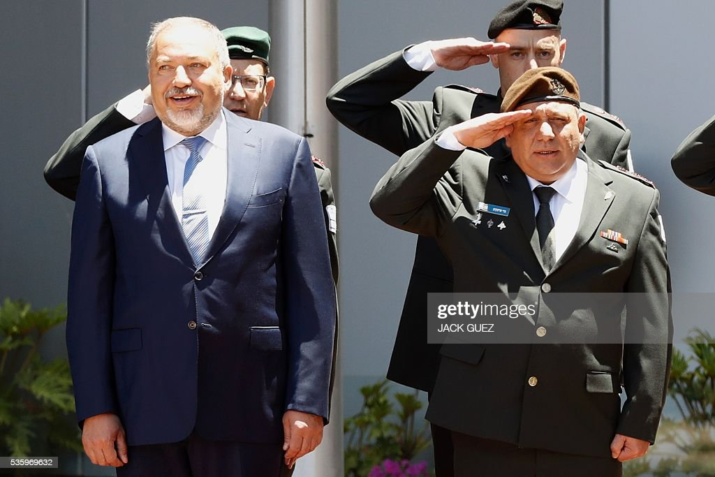 Israeli ultra-nationalist and newly appointed defence minister Avigdor Lieberman (L) and Israel's Chief of Staff, Lieutenant General Gadi Eizenkot (R) listen to their country's national anthem during the welcoming ceremony at the Defence Ministry in the city of Tel Aviv, on May 31, 2016. Lieberman assured he supported the creation of a Palestinian state after being sworn in as defence minister despite outrage over his appointment to the powerful post. / AFP / JACK