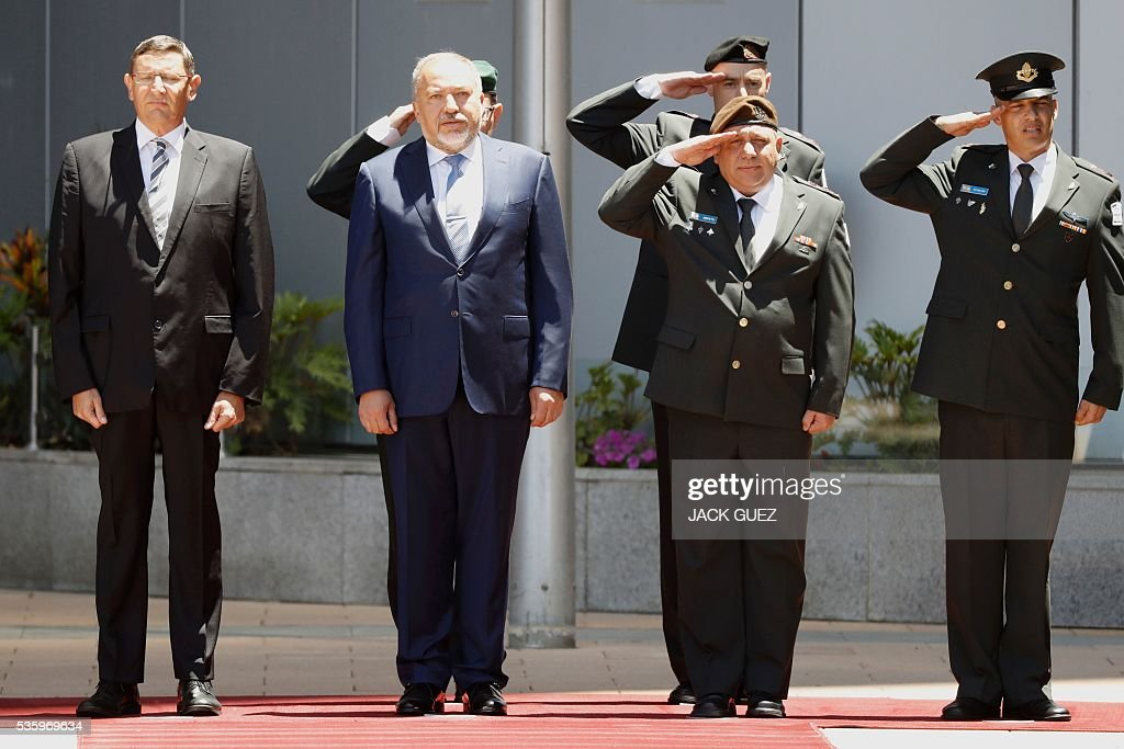 Israeli ultra-nationalist and newly appointed defence minister Avigdor Lieberman (2-L) and Israel's Chief of Staff, Lieutenant General Gadi Eizenkot (2-R) listen to their country's national anthem during the welcoming ceremony at the Defence Ministry in the city of Tel Aviv, on May 31, 2016. Lieberman assured he supported the creation of a Palestinian state after being sworn in as defence minister despite outrage over his appointment to the powerful post. / AFP / JACK
