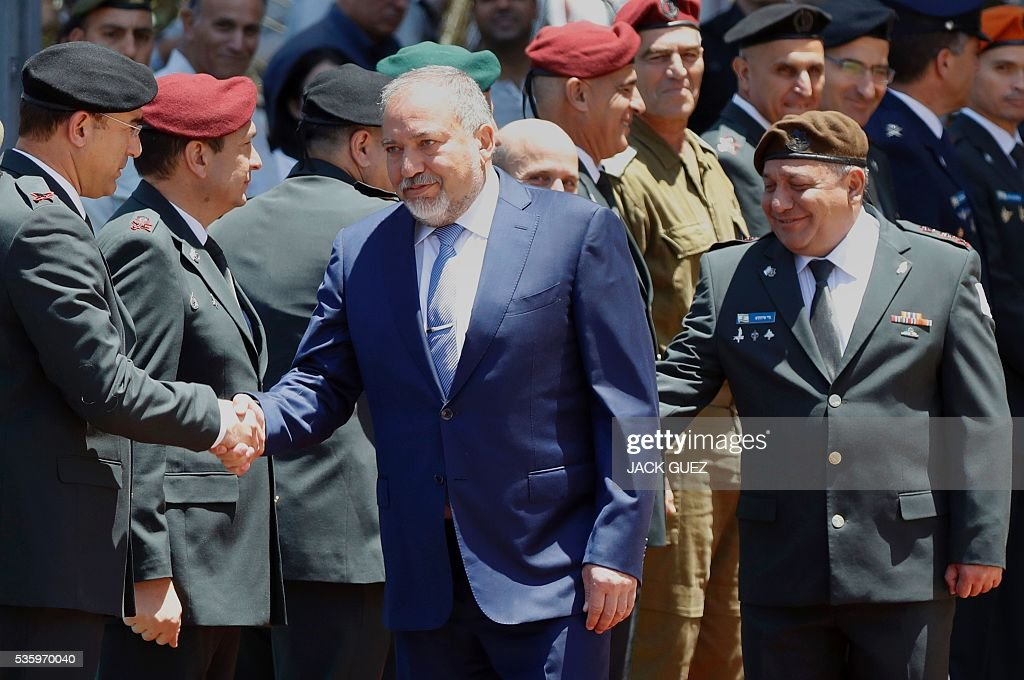 Israeli ultra-nationalist and newly appointed defence minister Avigdor Lieberman (C) and Israel's Chief of Staff, Lieutenant General Gadi Eizenkot (R) shake hands with the military general staff during the welcoming ceremony at the Defence Ministry in the city of Tel Aviv, on May 31, 2016. Lieberman assured he supported the creation of a Palestinian state after being sworn in as defence minister despite outrage over his appointment to the powerful post. / AFP / JACK