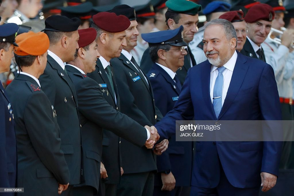 Israeli ultra-nationalist and newly appointed defence minister Avigdor Lieberman (R) shakes hands with the military general staff during the welcoming ceremony at the Defence Ministry in the city of Tel Aviv, on May 31, 2016. Lieberman assured he supported the creation of a Palestinian state after being sworn in as defence minister despite outrage over his appointment to the powerful post. / AFP / JACK