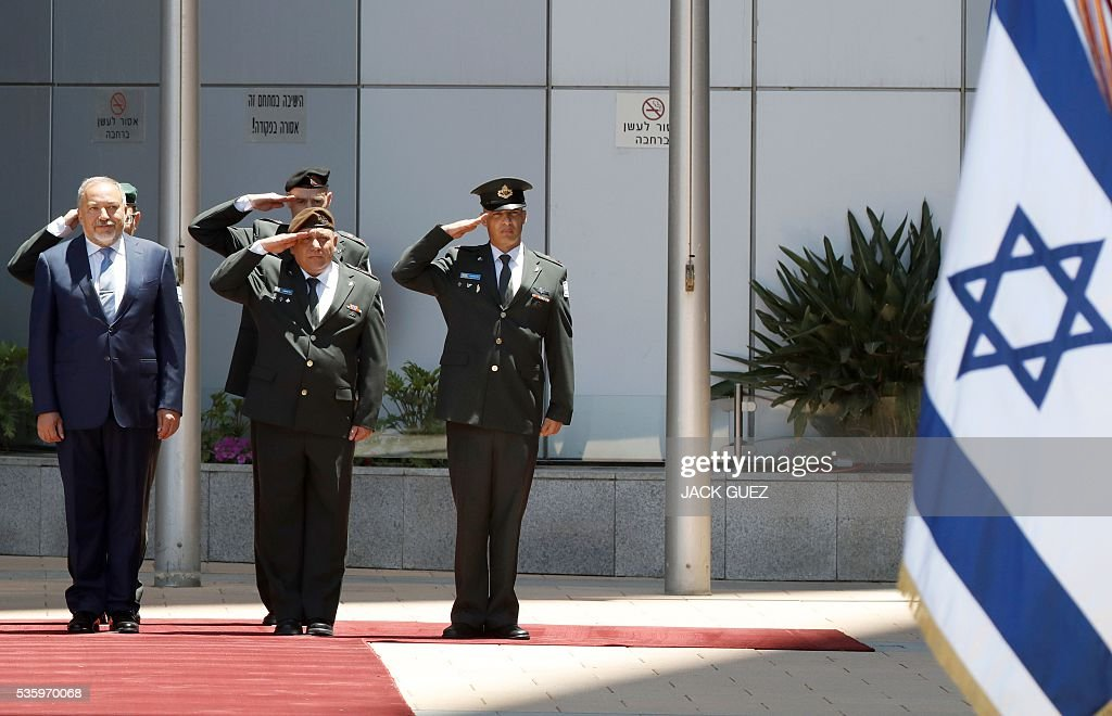 Israeli ultra-nationalist and newly appointed defence minister Avigdor Lieberman (L) and Israel's Chief of Staff, Lieutenant General Gadi Eizenkot (C) listen to their country's national anthem during the welcoming ceremony at the Defence Ministry in the city of Tel Aviv, on May 31, 2016. Lieberman assured he supported the creation of a Palestinian state after being sworn in as defence minister despite outrage over his appointment to the powerful post. / AFP / JACK