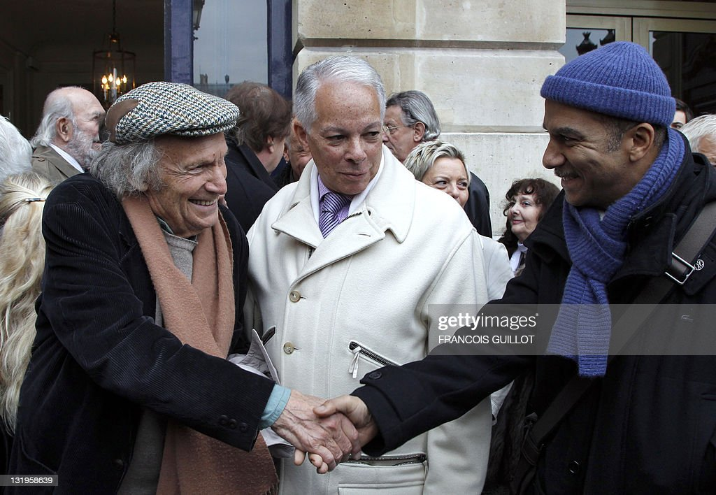 Israeli violonist Ivry Gitlis (L) salutes French actor Pascal Legitimus (R) beside Henri Salvador's nephew Clovis Salvador as they attend a ceremony to unveil a plaque to mark the building where French entertainer Henri Salvador had lived for 46 years, 6 place Vendome in Paris, on November 9, 2011.