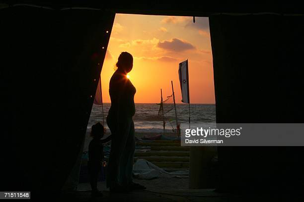 Israeli woman Ortal Malka holds her daughter's hand as she admires the sunset from the door of the large tent they share with other evacuees July 24...
