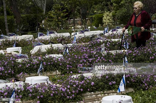 Israeli woman walks amid graves of killed soldiers at the Kiryat Shaul military cemetery in Tel Aviv on April 18 ahead of the start of Remembrance...