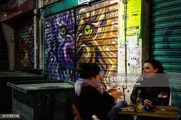 Israeli women enjoy at a local bar as they sit in front of a graffiti depicting Fanciful animals which was painted over a closed shutter at the...