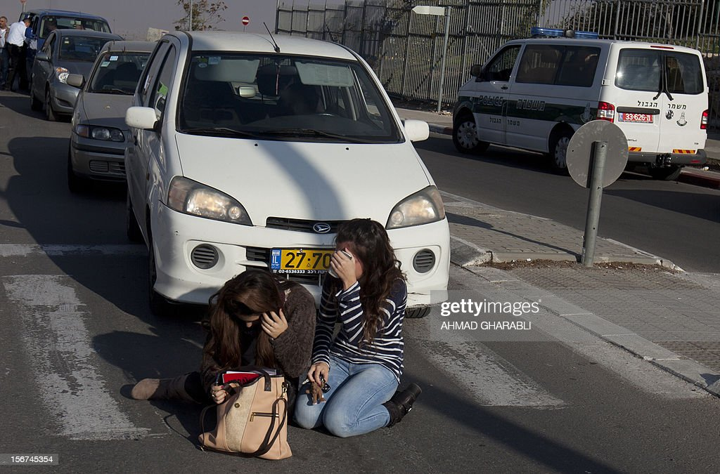 Israeli women take cover as air raid sirens sound around Jerusalem on November 20, 2012. A rocket struck just south of Jerusalem as UN chief Ban Ki-moon was to arrive for talks on ending the Gaza crisis, AFP correspondents said.