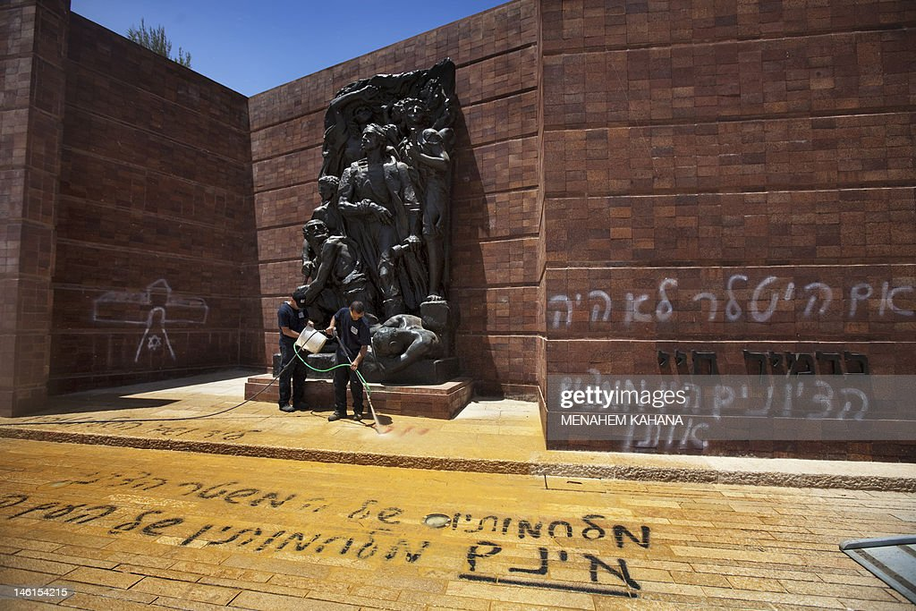 Israeli workers clean anti-Zionist Hebrew graffiti some thanking Hitler for the Holocaust and denouncing Zionism was sprayed at Jerusalem's Yad Vashem Holocaust museum compound June 11, 2012 in Jerusalem, with suspicion falling on ultra-Orthodox opponents of the state of Israel. Several slogans were sprayed on the red-brick Wall of Remembrance in Warsaw Ghetto Square, one of which read: 'The Zionist leadership wanted the Holocaust,' while the other said: 'If Hitler hadn't existed, the Zionists would have invented him (R).'
